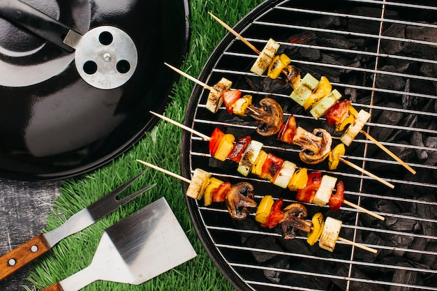 Preparation of grilled skewer with meat and vegetable on barbecue grill Free Photo