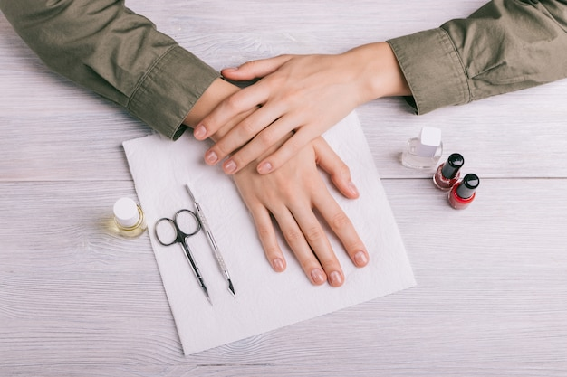 Preparation to manicure: women's hands, bottles of lacquer and other tools on the table Premium Photo