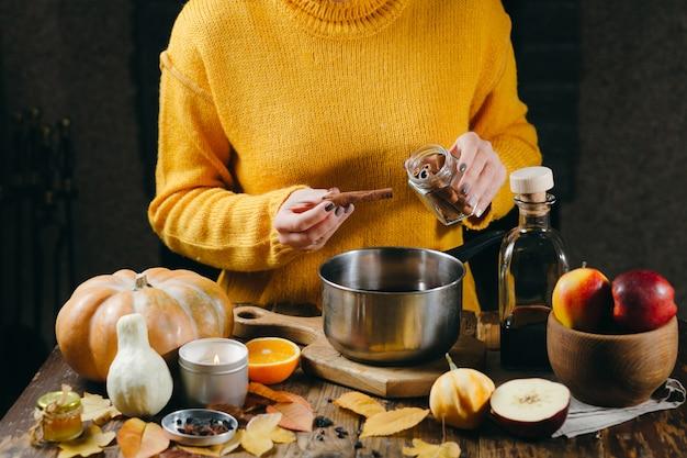 グリューワインの準備ホットグリューワインにシナモンの棒を追加する黄色いセーターの女性の手 Premium写真