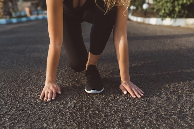 Preparation to run, start of pretty woman, hands near feets in sneakers on street. motivation, sunny morning, healthy lifestyle, recreation, training, outwork Free Photo