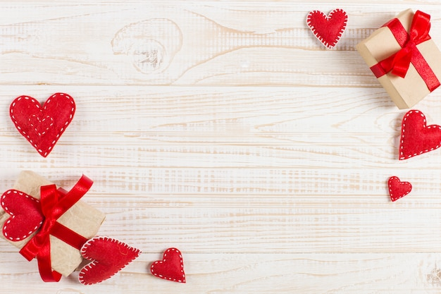 Preparation for valentine's day. red hearts and craft gifts on white wood. copy space Premium Photo