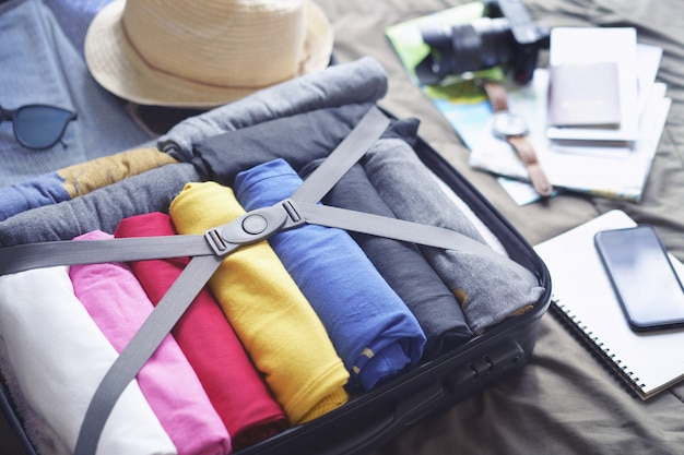 Prepare accessories for journey and travel to long weekend trip, packing clothes in suitcase bag on bed. Premium Photo