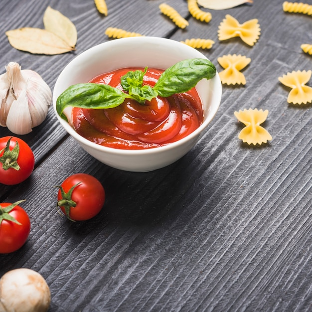 Prepared fresh tomato sauce with basil leaf on table Free Photo