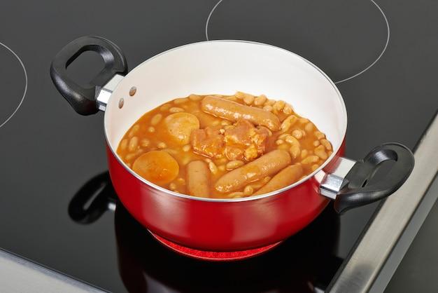 Preparing cassoulet in red ceramic pan Premium Photo