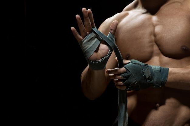 Hình ảnh võ sĩ ngực trần cơ bắp đang đeo găng tay chuẩn bị trận đấu