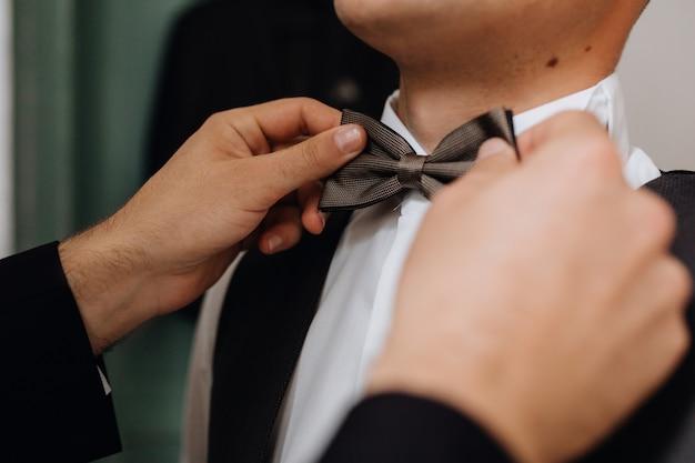 Подготовка к важному событию, надев галстук-бабочка, вид спереди Бесплатные Фотографии