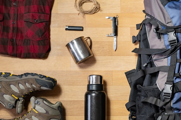 Preparing for a hiking trip: backpacking things and clothes flat lay. top view of trekking boots, tourist rucksack and camping acessories on the floor Premium Photo