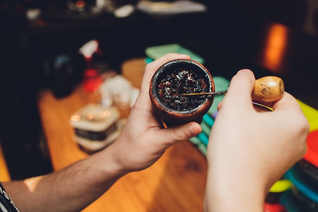 Preparing hookah for smoking, filling clay bowl with tobacco, male hands visible. Premium Photo