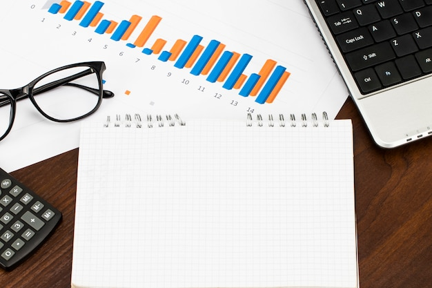 Preparing report. blue graphs and charts. business reports and pile of documents on wood table Premium Photo