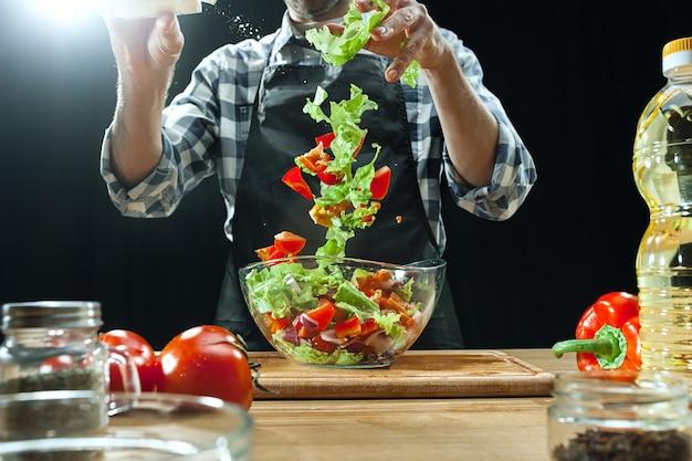 サラダを準備しています。新鮮な野菜を切る女性シェフ。調理プロセス。セレクティブフォーカス。健康食品、キッチン、サラダ、ダイエット、料理の有機コンセプト 無料写真