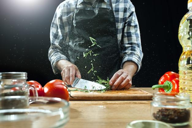 サラダを準備しています。新鮮な野菜を切る女性シェフ。調理プロセス。セレクティブフォーカス 無料写真