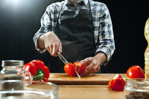 サラダを準備しています。新鮮な野菜を切る女性シェフ。 無料写真