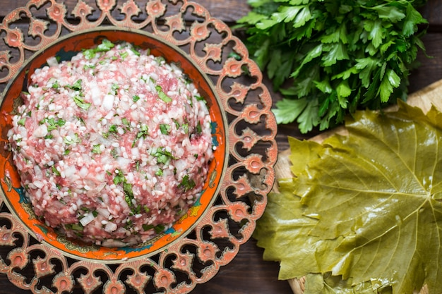 Preparing stuffed vine leaves with rice and meat, or traditional dolma.top view Premium Photo
