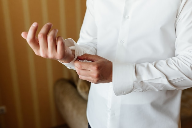 Preparing for wedding. groom buttoning cufflinks on white shirt before wedding. Free Photo