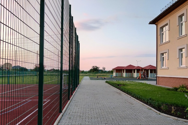 Preschool building yard with basketball court surrounded with high protective fence Premium Photo