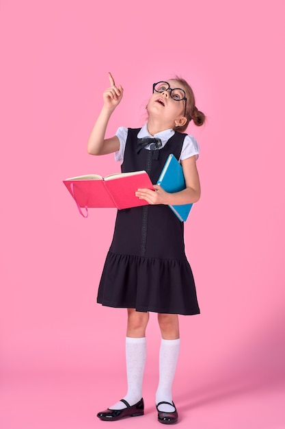 Preschool girl with glasses holding a book, raised her hand and finger up Premium Photo