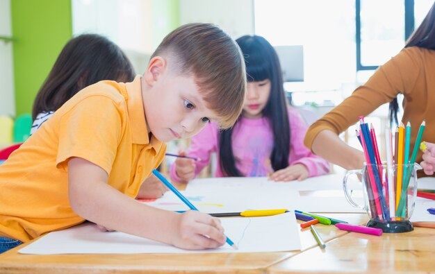 Preschool Kids Drawing With Color Pencil On White Paper On Table In  Classroom With Friends Premium