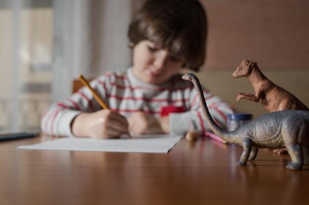 彼の家のテーブルに描く幼児 Premium写真