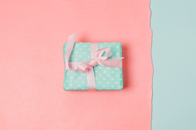 Present box over blue and peach backdrop Free Photo