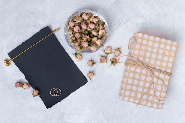 Present box near black paper and set of dry flowers Free Photo