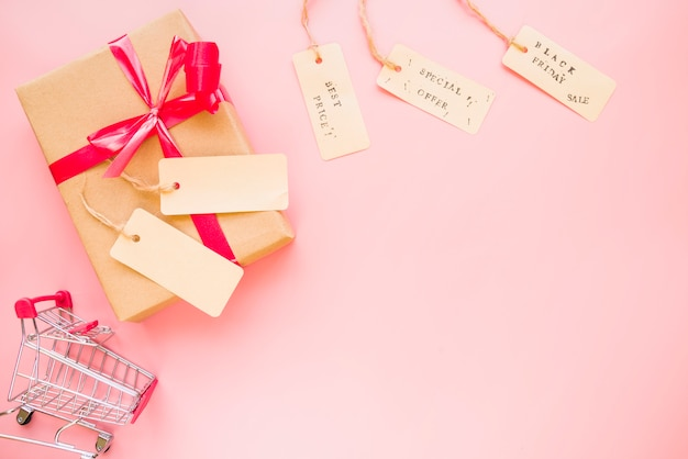 Present box with bow near shopping trolley and sale labels Free Photo