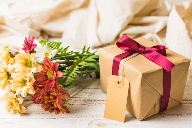 Present box with brown tag and flower bunch on table Free Photo