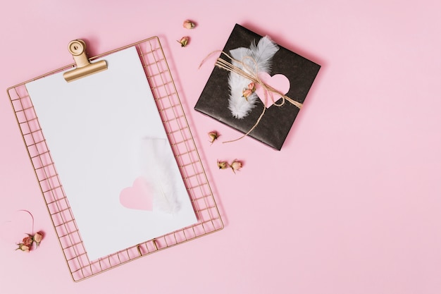 Present box with feathers and ornament heart near clipboard with paper Free Photo