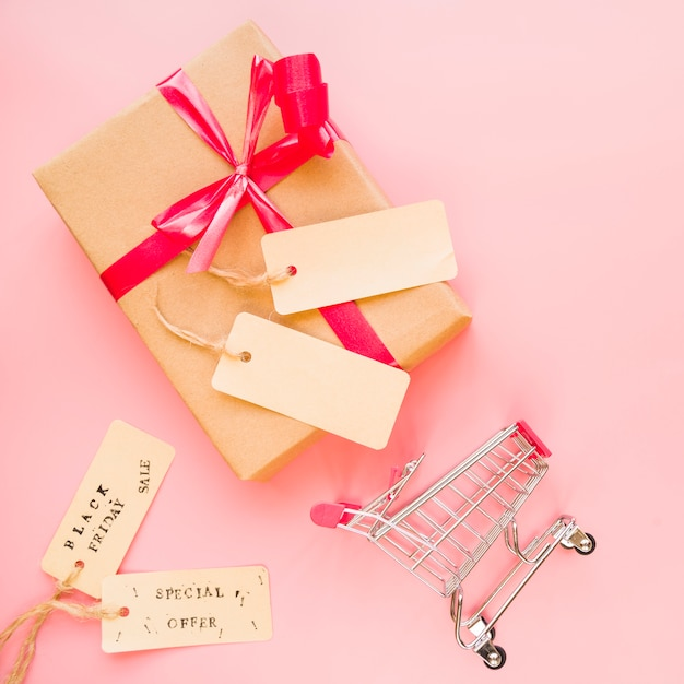 Present box with red bow near shopping trolley and sale labels Free Photo