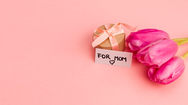 Present box with ribbon near note and flowers Free Photo