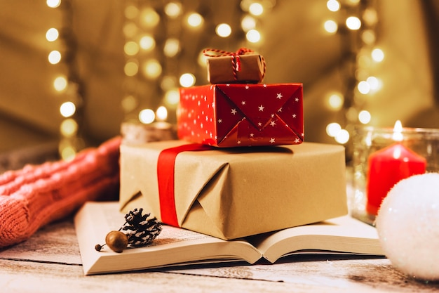 Present boxes on book near burning candle Free Photo