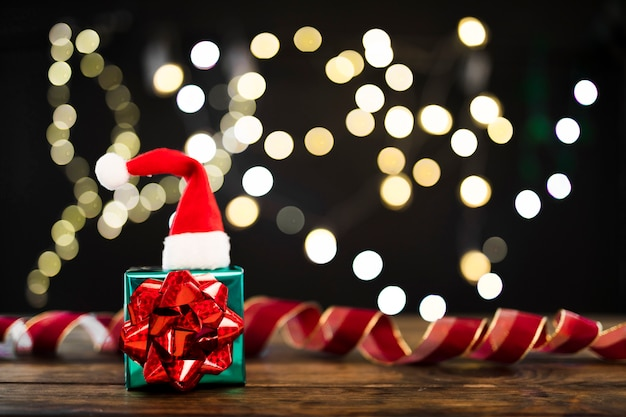 Present And Christmas Hat Near Ribbon And Garland Lights Photo