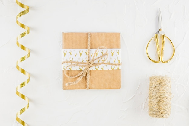 Present in craft paper near scissors and ribbon Free Photo