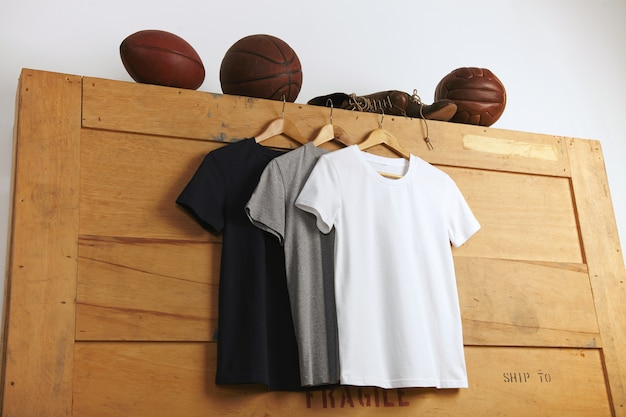 木製の配送ボックスの上にヴィンテージのフットボール、バスケットボール、バレーボール、古いスポーツレザーのブーツが付いた白、グレー、黒の無地の半袖tシャツのプレゼンテーション 無料写真