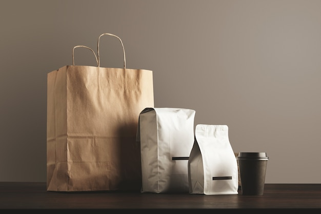 Presentation of retailer package set. craft paper bag, big pouch, small container and take away glass with cap. Free Photo