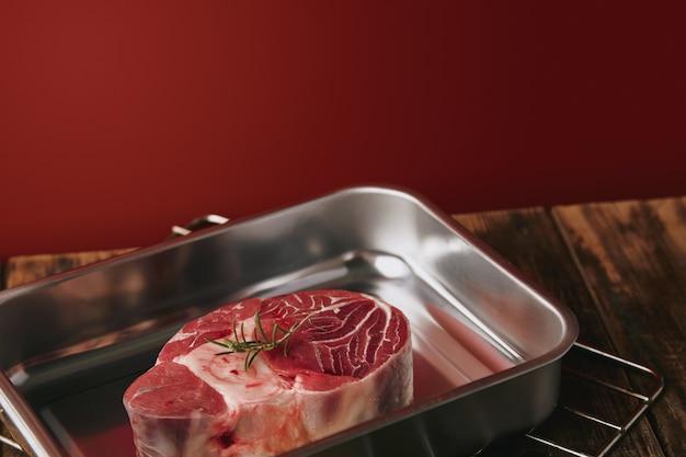Presentetion della bistecca di gamba angus cruda in padella in acciaio argento su sfondo rosso tavolo in legno Foto Gratuite