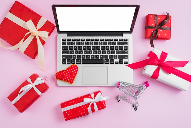 Presents and shopping cart around laptop and heart Free Photo