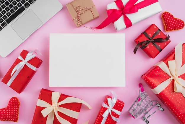 Presents and shopping trolley near paper sheet and laptop Free Photo