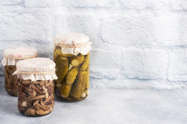 Консервация овощей в банках. продукты брожения. заготовка огурцов и грибов на зиму. скопируйте пространство. Premium Фотографии