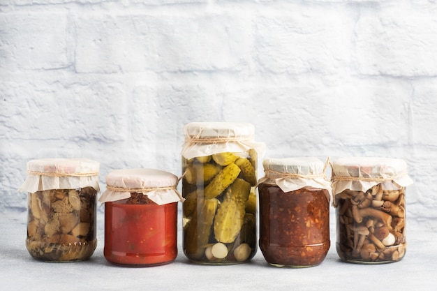 Консервация овощей в банках. продукты брожения. заготовка помидоров и ягод, грибов на зиму. скопируйте пространство. Premium Фотографии