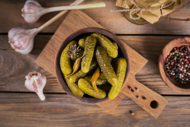 Консервирование маринованных огурцов, приправ и чеснока на деревянном столе. здоровая ферментированная пища. овощные консервы домашние. Premium Фотографии