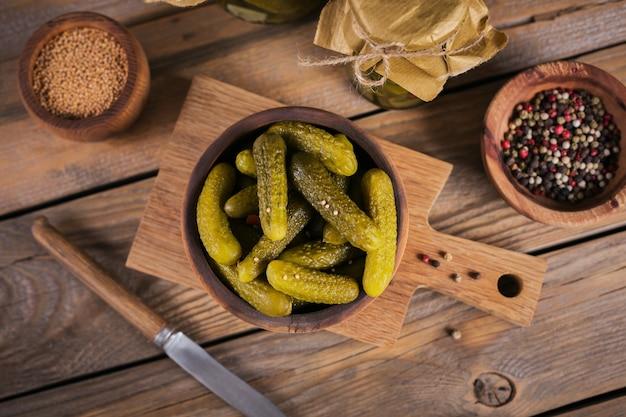 Консервирование маринованных огурцов, приправ и чеснока на деревянном столе Premium Фотографии
