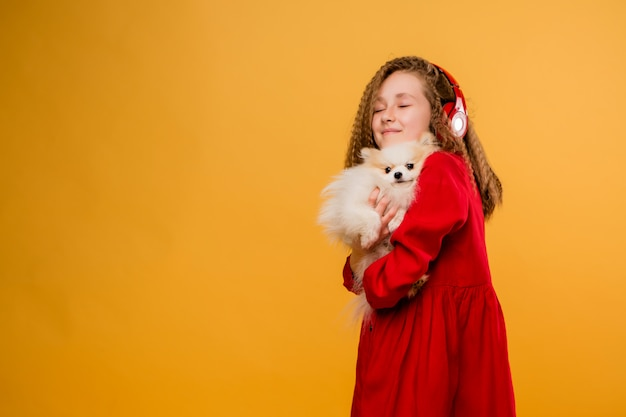 Preteen girl holding a small dog in her hands Premium Photo