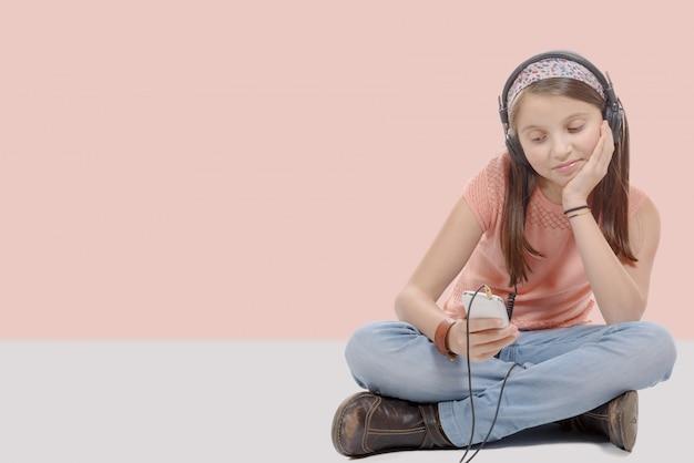 Preteen girl listening to music with his smartphone, sitting cross legged Premium Photo