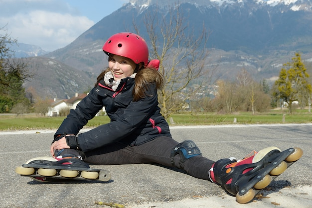 Preteen girl in rollerskate sitting on the road Premium Photo