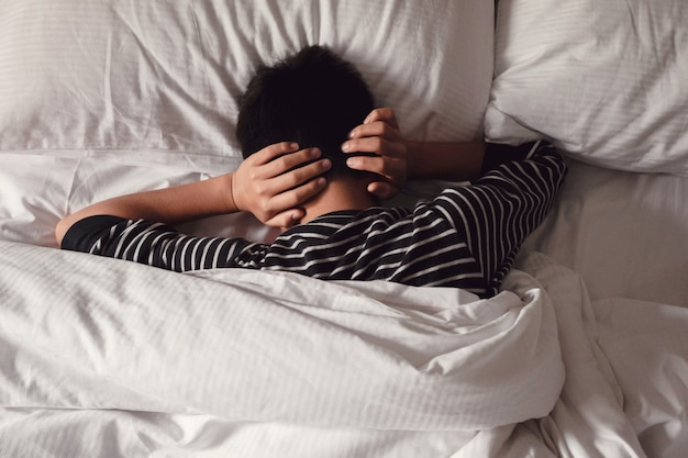Preteen tween boy covering ears with his hands in bed, adhd, autism,sleep disorder, mental health in children, not want to hear, wake up kid for school concept Premium Photo