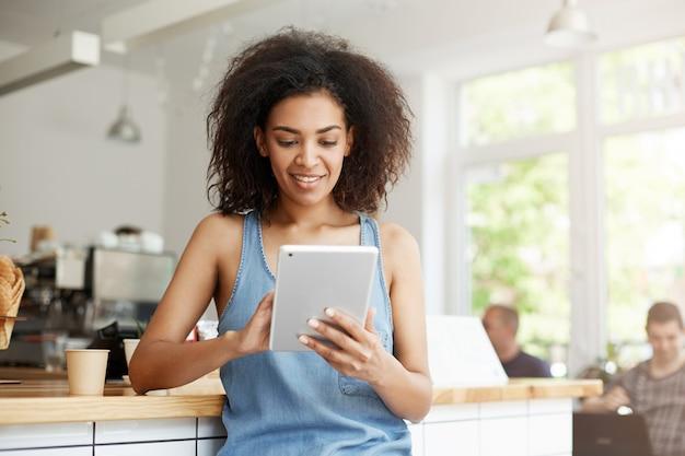 Довольно африканская студентка отдыхая в кафе усмехаясь смотрящ экран таблетки. Бесплатные Фотографии