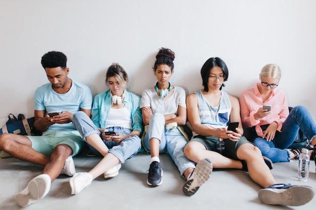 Ragazza abbastanza africana offesa perché gli amici non le prestano attenzione mentre usano i loro telefoni. triste studentesse con i capelli ricci seduti tra compagni di università con le braccia incrociate. Foto Gratuite