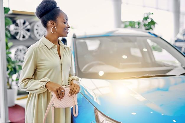 예쁜 아프리카 아가씨는 자동차 쇼룸에서 자동차를 좋아했습니다. 프리미엄 사진