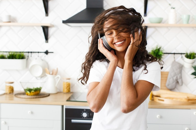 Pretty african woman whirls her head and listens to music via headphones in the kitchen Free Photo