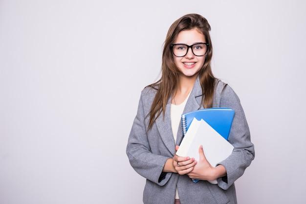 白い背景に笑みを浮かべていくつかの本の近くの大きなメガネでかなり、若い学生 無料写真